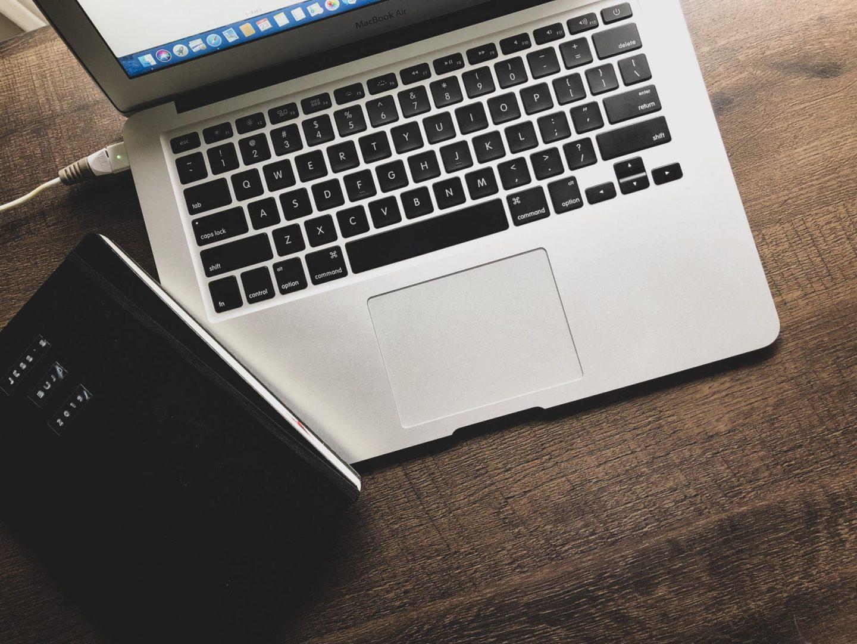 laptop and bullet journal on desk