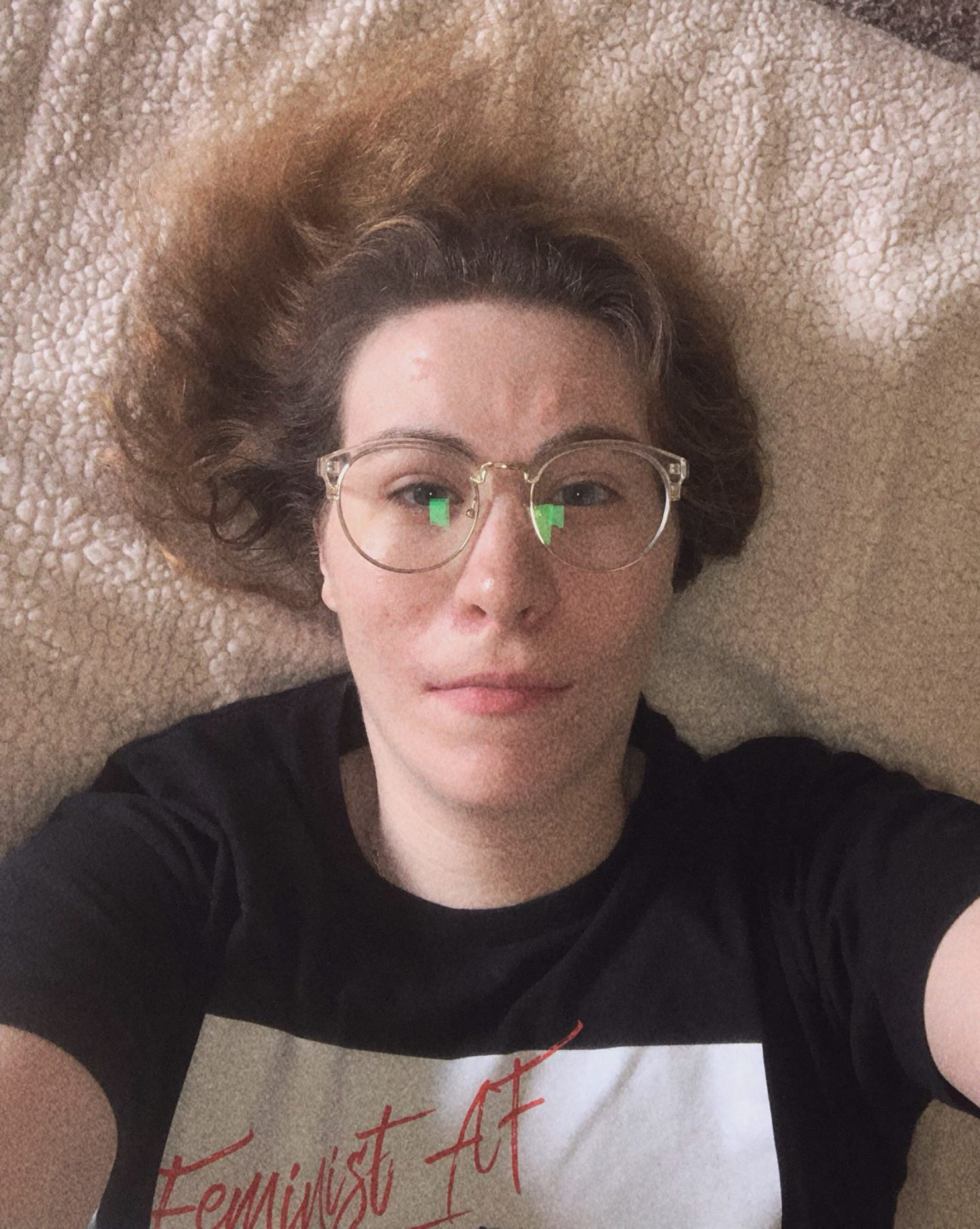 Girl laying on bed taking a selfie