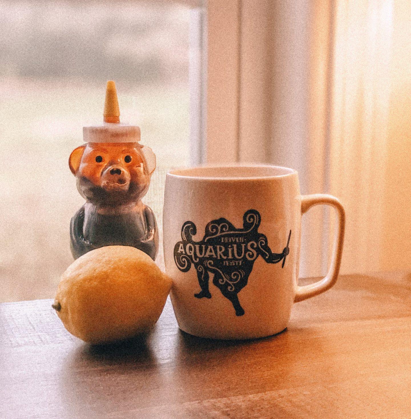 cup of hot lemon water, lemon, honey bottle