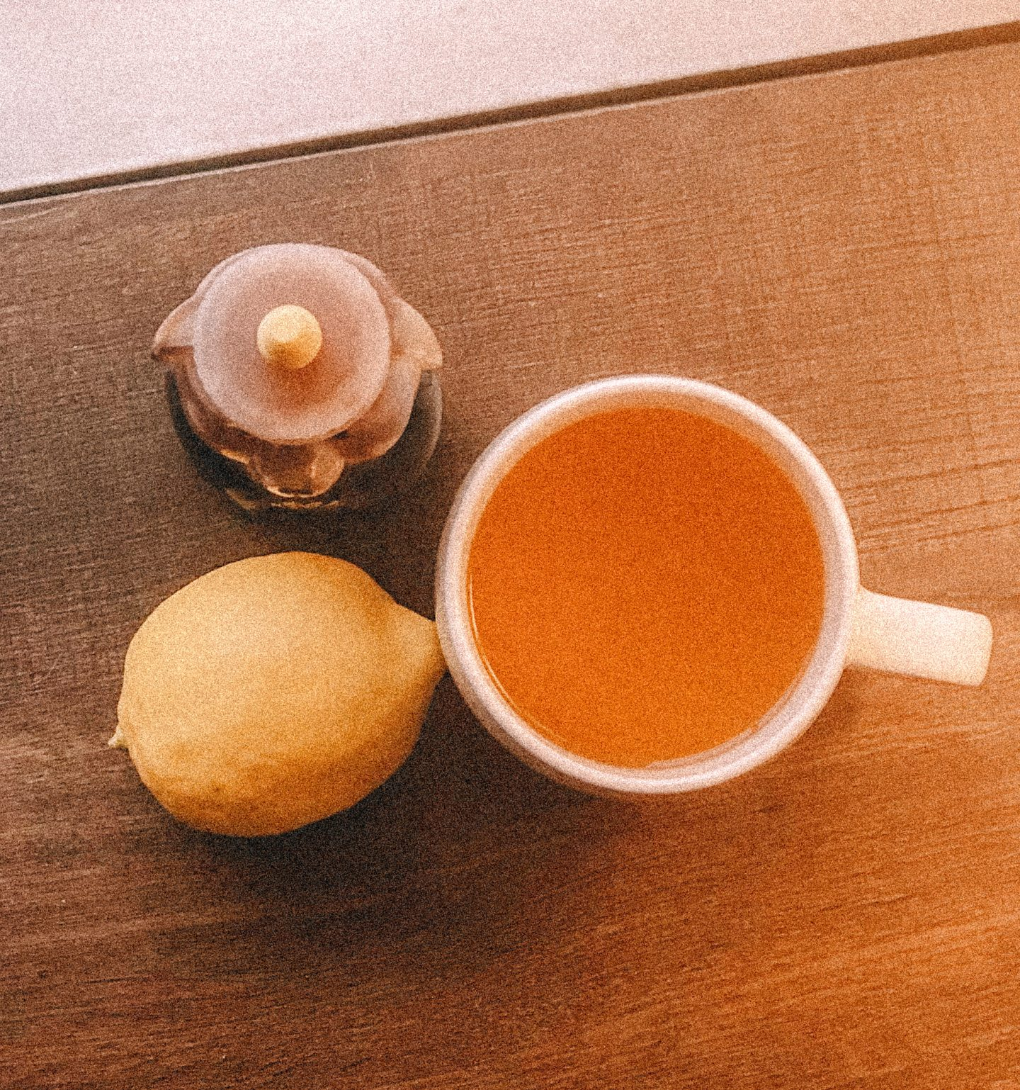 above view of cup of hot lemon water, lemon, and honey bottle